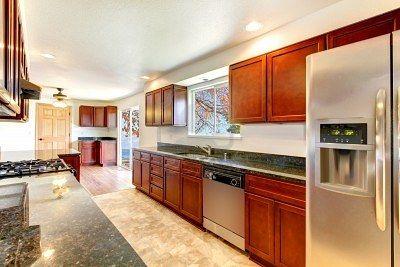 Amplia cocina luminosa, con oscuros gabinetes de cerezo y acero inoxidable electrodomésticos. Foto de archivo