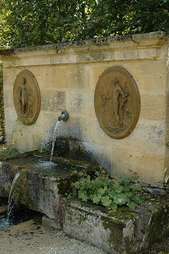 Water fountain in the gardens of the Château de Losse Dordogne France.  The positioning of the bas-reliefs either side of this water feature gives it more importance.