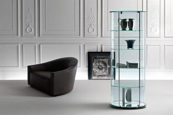 GlazenDesignTafel.nl | Glazen vitrine van FIAM in gebogen glas met vier legplanken in helder glas. De vitrinekast is voorzien van een deurslot. De basis wordt geleverd in drie varianten: verzilverd, mat zwart of geëmailleerd.