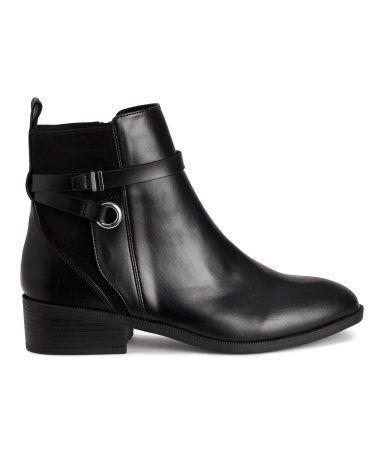 Sort. Boots i imiteret læder med detaljer i imiteret ruskind. De har ankelhøjt skaft med strop bagpå, dekorative remme og lynlås i siden. For i satin og