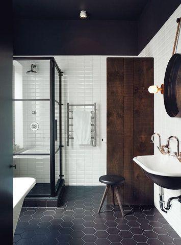 De estilo industrial, este banheiro apostou em piso de azulejos pretos geométricos, porta de madeira escura, espelho tipo pêndulo, e box de vidro transparente.: