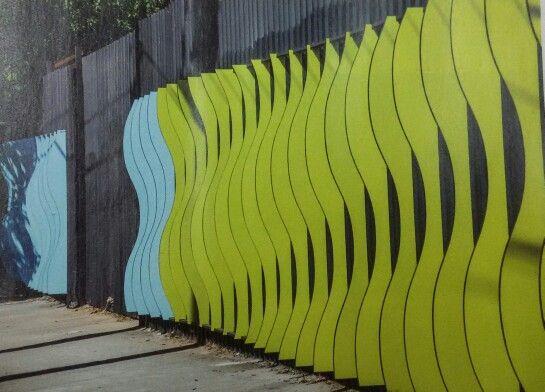 Tapume de obra em SP. Construtora Kallas e estúdio BijaRi. Placas em OSB no formato de ondas.