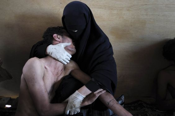 """""""It's a photograph of a burka-clad woman holding a wounded relative in embrace in a hospital in Sana, Yemen. We can't see their faces—his is buried in her chest, hers is covered by the burka—but their bodies tell the story: he is sitting limp, exhausted, in pain, she is hugging him protectively, consoling. """" via: http://natpo.st/wiggJu"""
