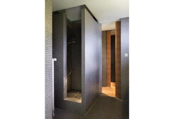 Una delle stanze da bagno dell'abitazione di Ralph Germann, situata a Montreux, Svizzera. Lo spazio è rivestito in pasta di vetro, con un mosaico a tasselli blu scuro che prosegue nell'ampio box doccia
