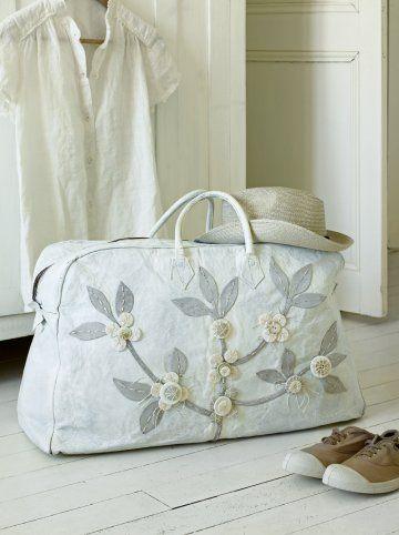 Un sac en cuir chiné peint en blanc et décoré avec des branches de cerisiers en cuir et en boutons
