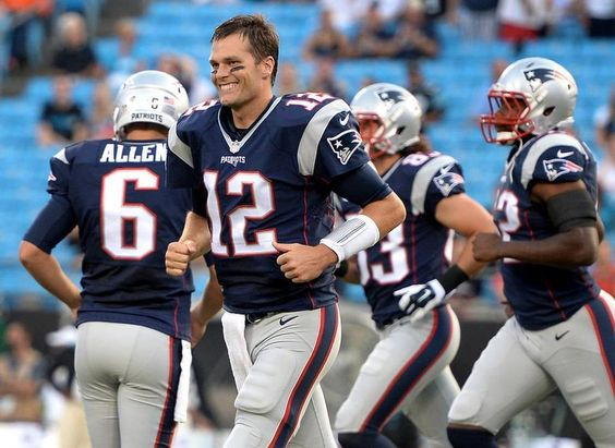New England Patriots quarterback Tom Brady smiles as he runs onto the field for first quarter action vs the Carolina Panthers at Bank of America Stadium in Charlotte, NC on Friday, August 28, 2015.