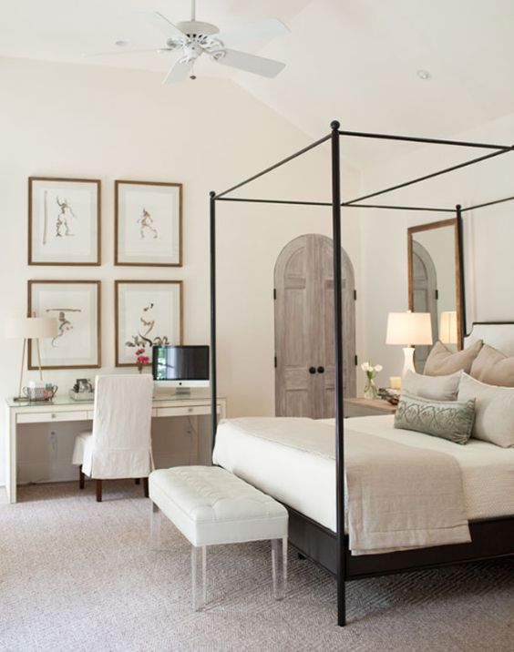 Stunning romantic and feminine bedroom with arched wood doors painted light grey, a vanity table with a quartet of framed art above it, and a delicate iron canopy bed with soft linens in pastels. Romantic European Farmhouse Bedroom Decor Ideas!