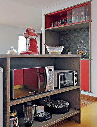 Nesta outra cozinha, a bancada é de concreto e o fogão ficou envolvido por esta caixa do mesmo material. Os armários, envolvidos por concreto, são feitos do mesmo material da porta.