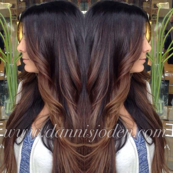 Dark brown melting into warm chocolate brunette balayage highlights to create a subtle ombré effect.