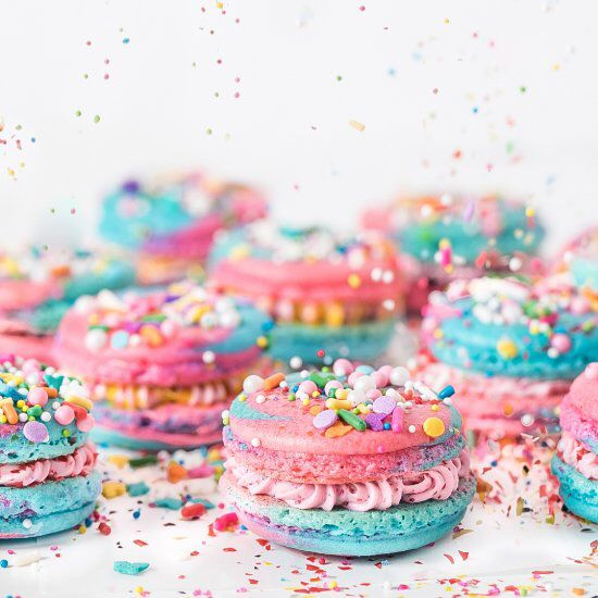 Bright and colorful almond Unicorn Macarons with a glitter cotton candy buttercream filling.