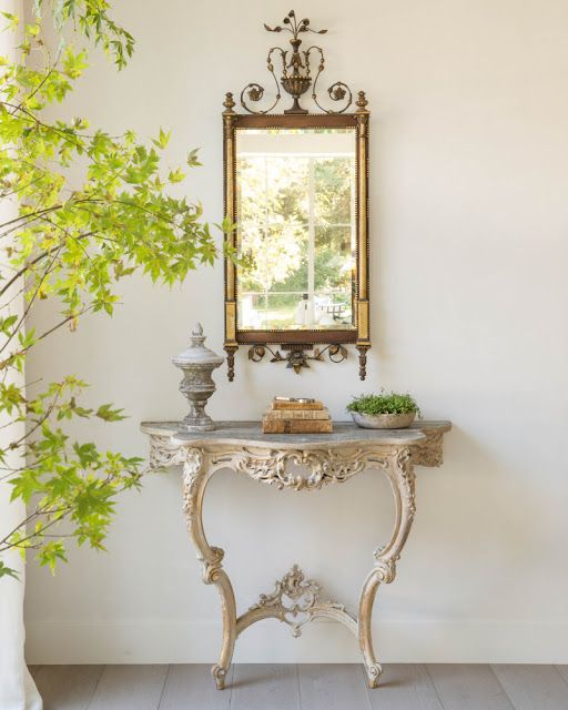 French Country decor in a modern farmhouse elegant entry with antique ornate table, mirror, and greenery in Malibu farmhouse by Giannetti Home and Brooke Giannetti. Photo by Lisa Romerein. #giannettihome #frenchcountry #antiques #frenchfarmhouse #frenchmirror #consoletable #decorideas #interiordesign