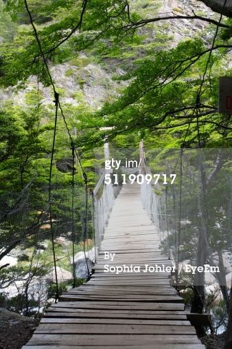 Stock Photo : Wooden hanging bridge over a river