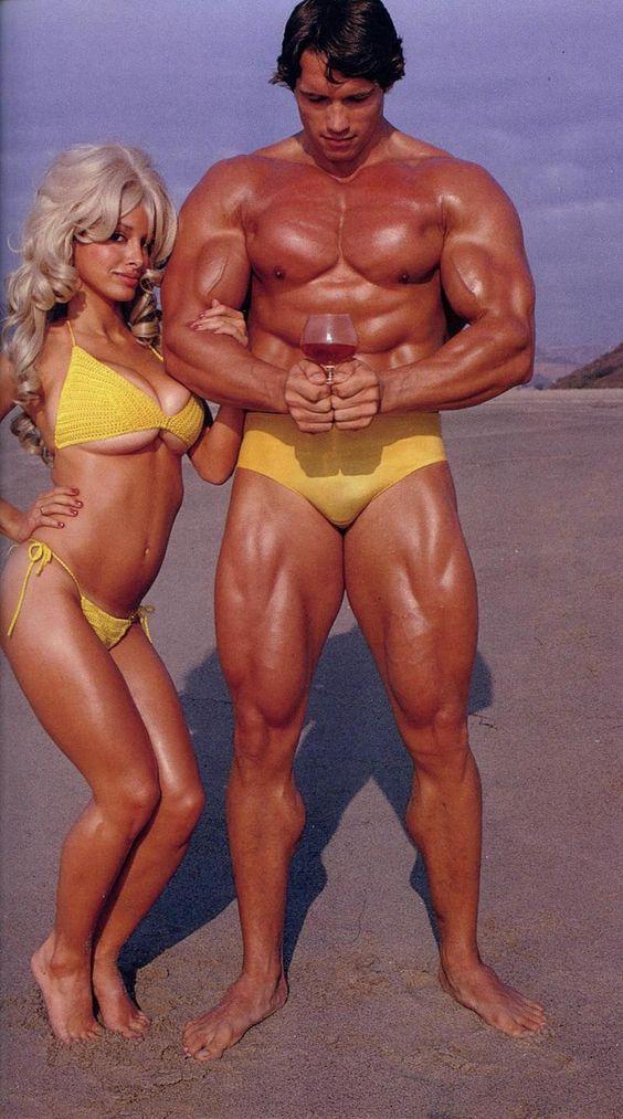 Duelo de pectorales. Arnold Schwarzenegger sacando músculo en las payas de California junto a una despampanante rubia con más pectorales que el austriaco. | Playboy
