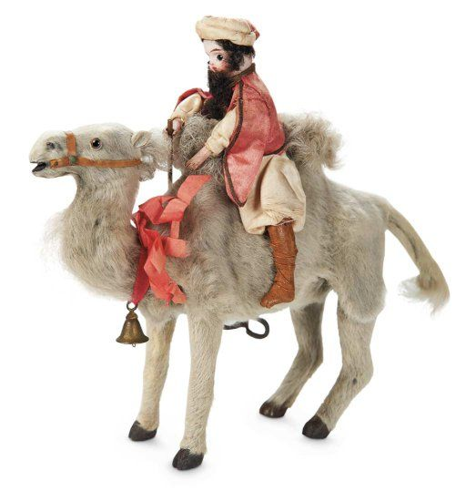 "French Mechanical Toy ""Sultan Riding a Camel""---wearing original silk Sultan's costume and turban, leather boots. When wound, the camel rises and moves up and down in a vigorous manner, and the Sultan bobs back and forth.  French, circa 1880, maker unknown of the series of amusing ""jumping animal"" keywind toys, some made with animal only, and others with a bisque rider; another example with Spanish rider on a horse had an original box label ""Le Picador Exposition Universelle Paris 1878""…"