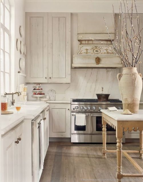 Magnificent white kitchen with detailed range hood, antique French work table and design by Kay O'Toole. #whitekitchen #frenchcountry #antiques #sophisticated