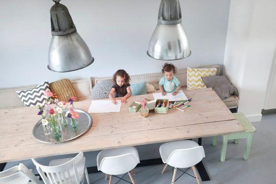 grande table de repas en bois, deux chaises RAR eames blanches, deux grandes suspensions industrielles, une banquette avec des coussins graphique et deux jeunes enfants qui dessinent