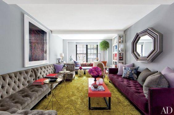 Este outro ambiente investe em um cinza quente com várias cores complementares ricas. O tapete esverdeado emoldura o ambiente, finalizado pelo sofá roxo.