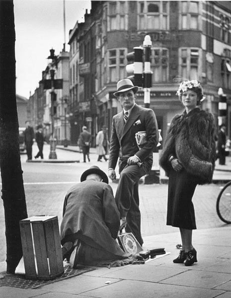 Wolf Suschitzky: Shoe Shine, Charing Cross Road, London, 1936  I don't think the gentleman liked having his photograph taken. His lady, however, seems to have posed for me.
