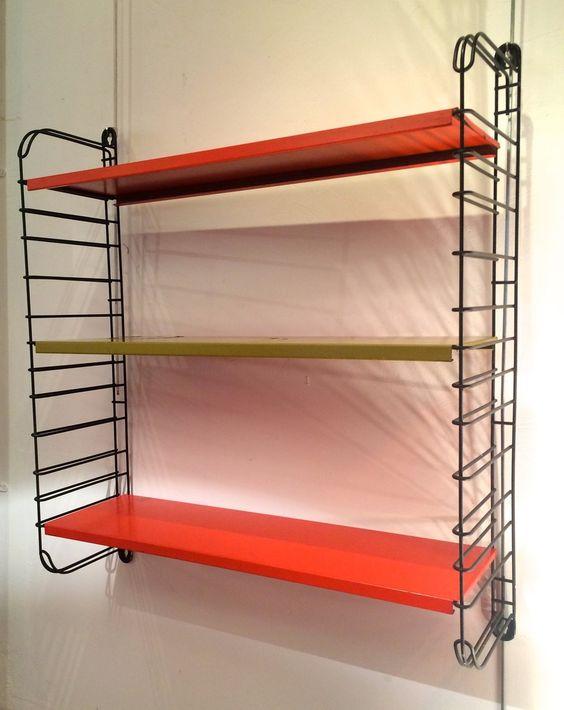 Série de trois étagères en métal réglables, deux oranges et une jaune (dégâts peinture), reposants sur deux montant Eiffel noirs. Hauteur 77 cm / Largeur 67 cm / Profondeur 20 cm  http://www.antique-art-versailles.fr/annuaire/brokn-design/