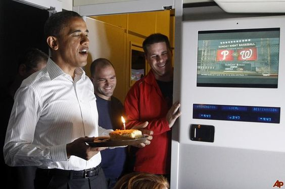 """President Obama, standing with Deputy National Security Adviser Ben Rhodes and Communication Director Dan Pfeiffer, sings """"Happy Birthday"""" in the press cabin on Air Force One as it flies back to Andrews Air Force Base"""