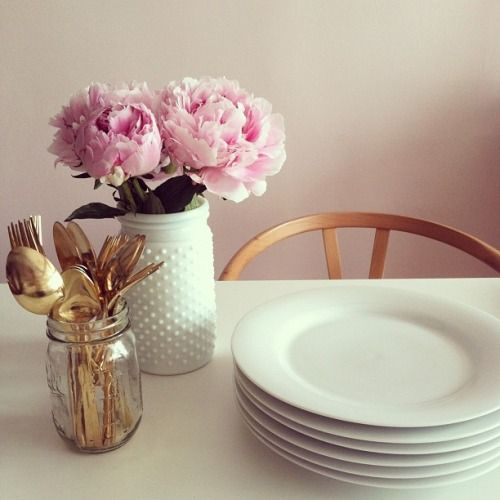 Flowers in the kitchen and gold kitchen utensils.