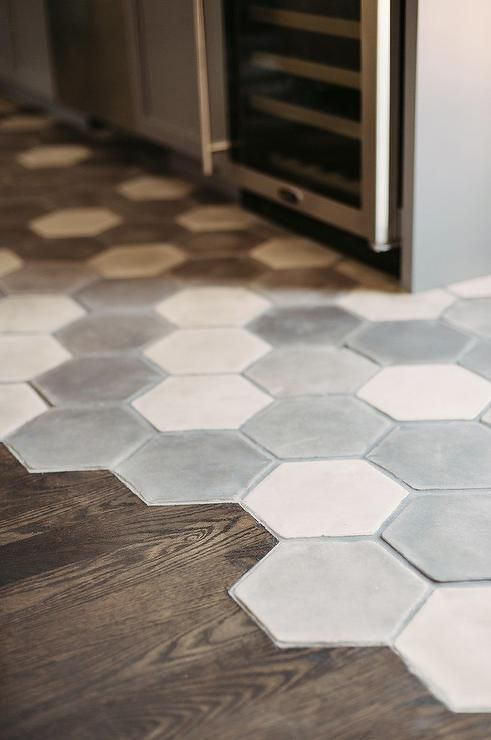 Fantastic gray kitchen features a white and gray hex concrete tiled floor which seamlessly transitions into a stained oak wood floor which leads to the dining space.:
