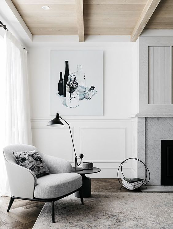 Gray and white room with gray chair, fireplace surround, beamed ceiling, black accents