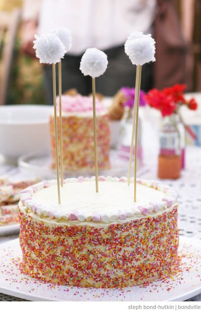 Sprinkle cake with pom pom toppers and mini marshmallows by Steph Bond-Hutkin