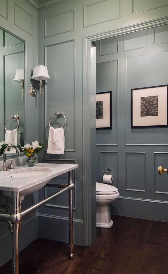 Gray paneled bathroom with white marble top sink on chrome base.