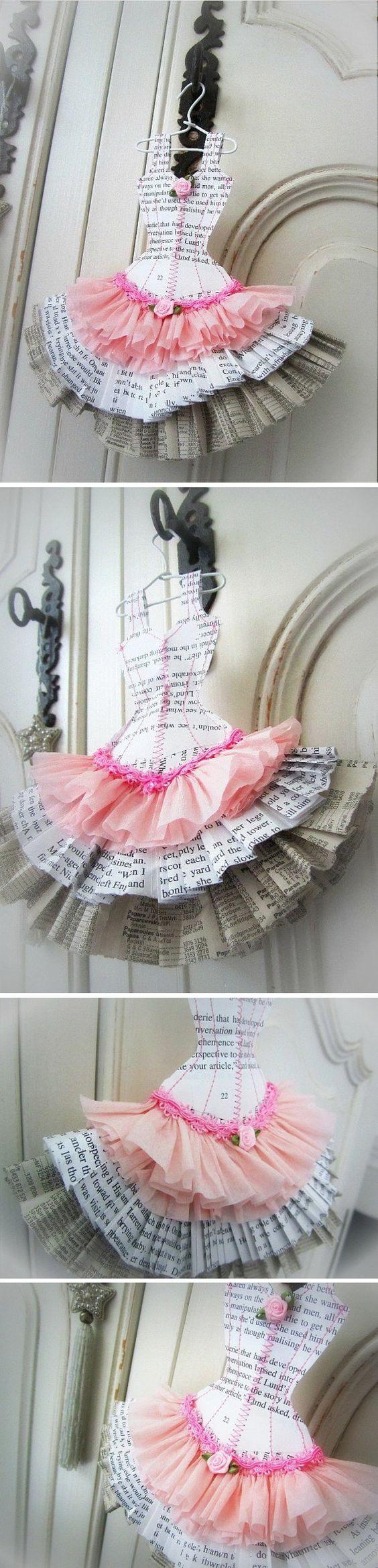 Robe faite à partir de pages de papier recyclé (romans, annuaires...) et de papier crépon. Elle est cousue avec du fil de coton rose et est soulignée d'un galon rose et de deux fleurs de satin rose. Elle mesure 19 cm de hauteur x 18 cm de largeur et est livrée avec son petit cintre blanc.