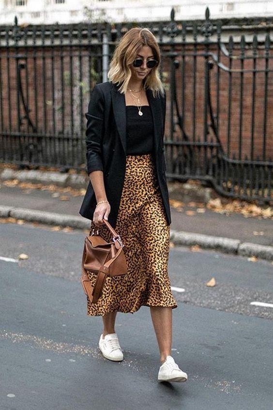 Falda de estampado animal con blazer negro y zapatillas blancas.