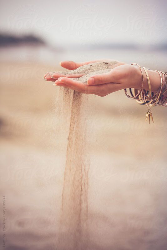 Woman letting sand fall through her fingers.