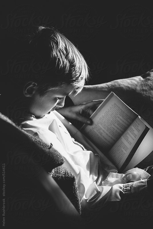 A black and white image of a pre-teen boy reading a book. by HelenRushbrook | Stocksy United