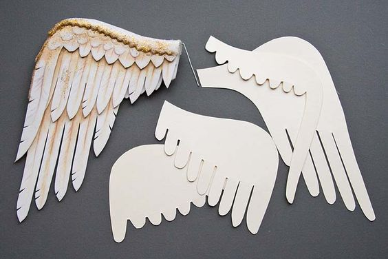 Draw a bird's wing, brake it down into four levels of feathers, and make cardboard templates for tracing onto the foam. The craft foam is very easy to work with, and take colour from pencil crayons and paint beautifully. cut a strip of felt with scalloping shears to cover the top edges of the foam, then totally smeared the felt with sparkle paint so it wouldn't get fuzzy or fray.