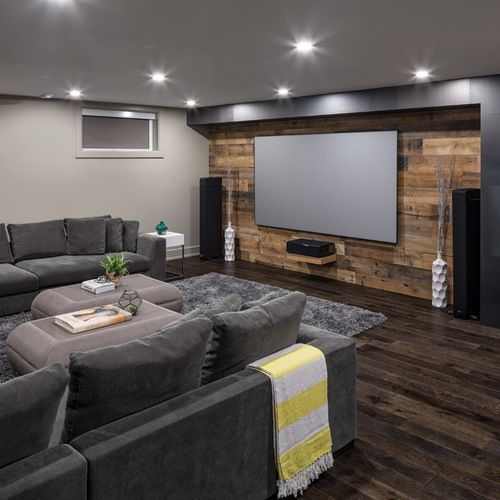 There are couches around the outside here and space on the inside for your drinks and snacks. With the wood background wall and plenty of space on the screen you'll love watching movies here.