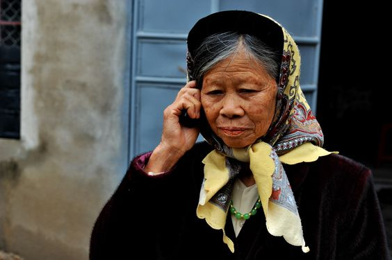 Old lady in the traditional clothes using her cell phone.