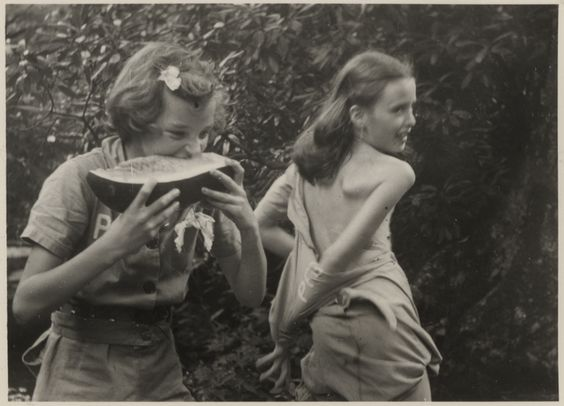 [Two unidentified girls, one eating watermelon, the other disrobing]: