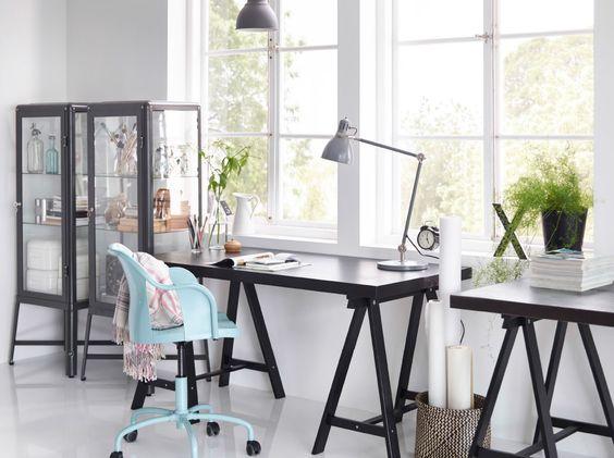 Um escritório em casa com secretária TORNLIDEN em preto, vitrina FABRIKÖR em cinzento escuro e cadeira giratória ROBERGET em azul.