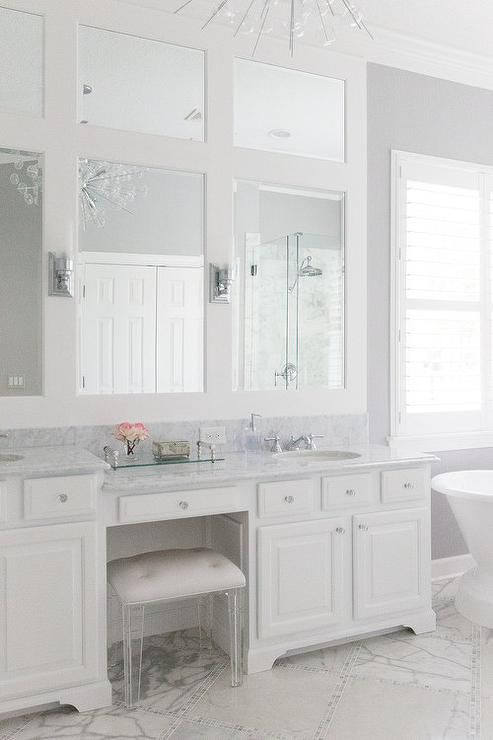 Beautiful White Bathroom Boasts A Lucite Vanity Stool Placed On Marble Diamond Floor Tiles B Bathroom With Makeup Vanity Vanity Stool Bathroom Cabinets Designs