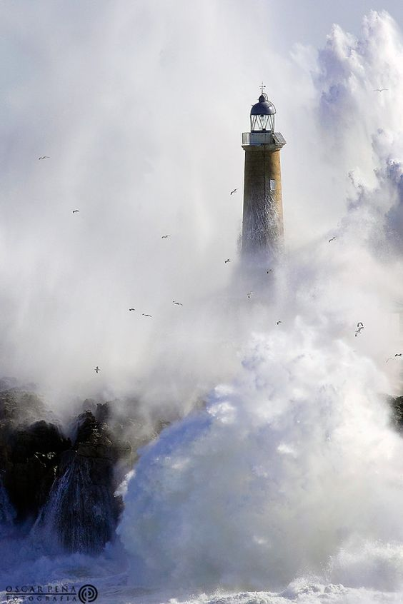 Storm - crashing waves surround a lighthouse on the ...