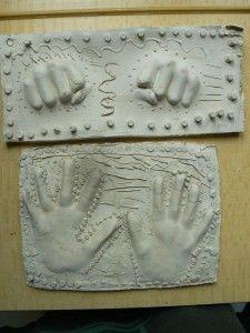 Première étape : imprimer sa main dans une plaque d'argile. Puis souligner la forme par un décor gravé. Deuxième étape : Couler le plâtre. Puis démouler ...