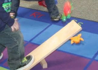 Make a  teeter board (see saw catapult) with wood blocks. Step on one end to make bean bags and small toy animals fly. Then - Can you catch them? - Pinned by Lessonpix.com