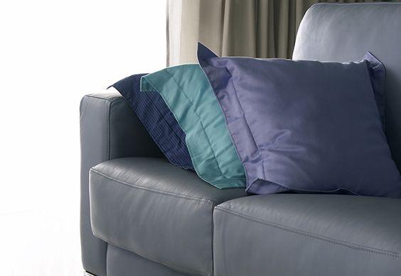 Sofá cinza e almofadas azul marinho, lilás e verde água.