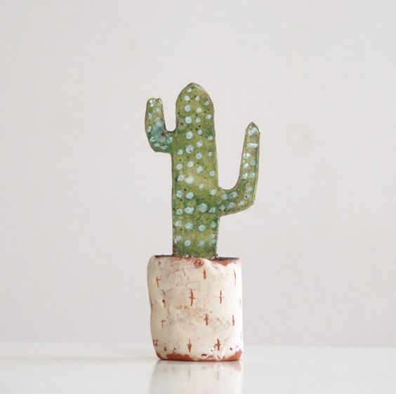 This ceramic cactus hand built of terracotta , decorated with engobes, fired,then glazed with transparent and green glazes and fired again.  Lead free.