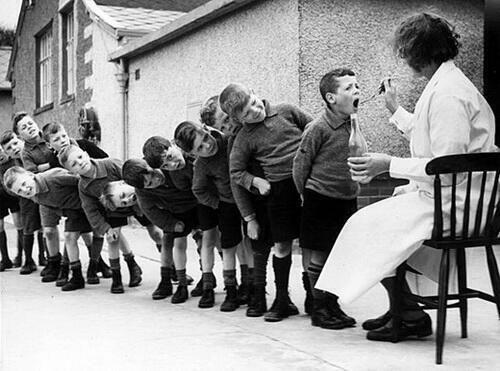 Kids line up for their weekly dose of fish oil, 1960. / Crianças em fila para sua dose semanal de óleo de peixe, 1960