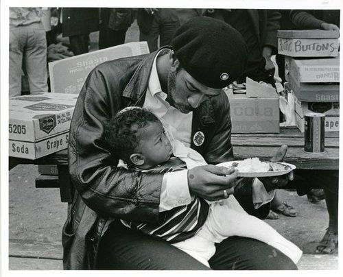 "A Black Panther feeds his son at the ""Free Huey"" rally in Oakland, California. February 17, 1968."