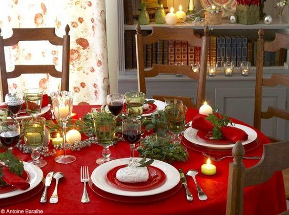Le rouge , un thème incontournable à Noël. Synonyme de déco chaleureuse, on le retrouve ici sur la nappe mais aussi sur les assiettes. Des branches de lierre font quant à elles office de ronds de serviette et sont disposées autour des photophores.