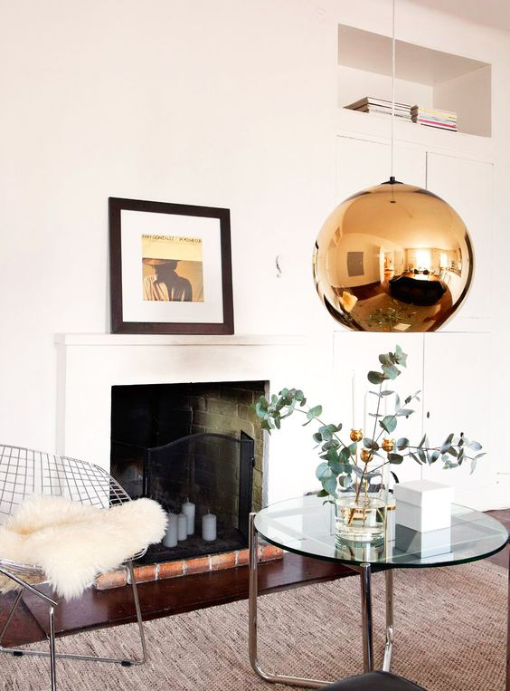 Living room with white walls, dark wood floors, fireplace with black and red bricks, glass coffee table, grey textured rug, silver chair, plants, and large gold light fixture