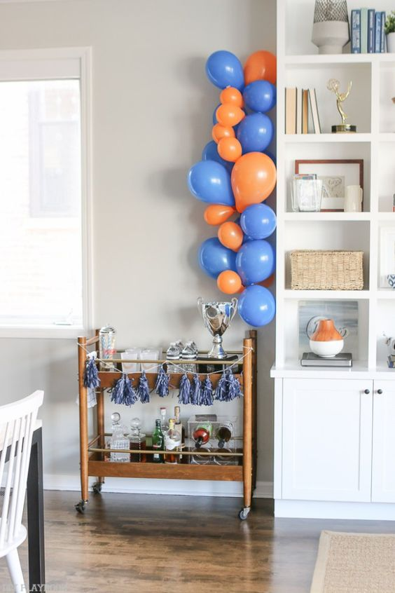 Create a bar cart and balloon garland at your next football watch party. Love this idea to make a little drink station and use your team's colors for extra pizzazz!