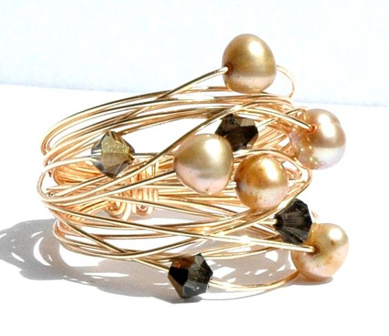 Gold Pearl Wire Wrap Ring / Gold Nest Pearl Ring / Wire Wrapped Ring with Gold Wire Freshwater Pearls and Black Diamond Swarovski Crystals  This ring is from a series of wire wrapped rings Ive made recently. Influenced by my modern surroundings from moving to Germany and their modern outlook on design. This one is made with golden/ black diamond colored Swarovski crystals, champagne colored freshwater pearls and gold wire. This one is a size 8. Please specify your size at checkout. X-Small…
